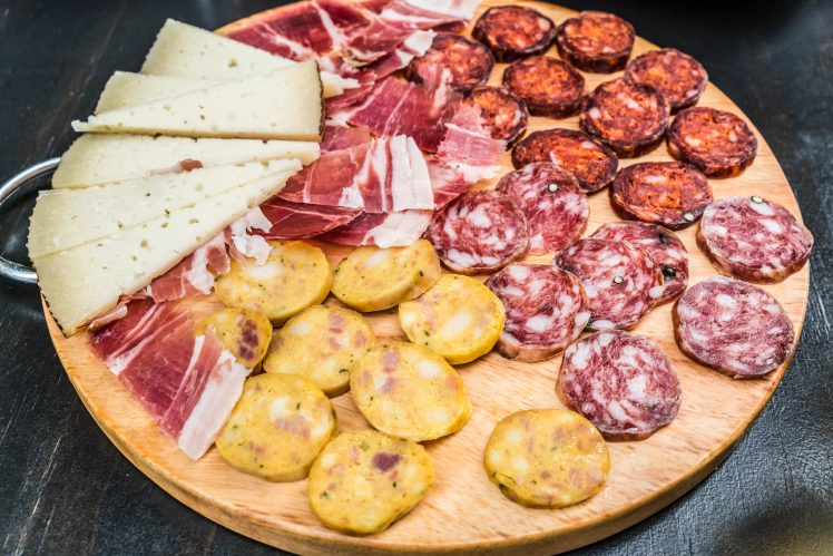 Typical cured ham, sausage and cheese plate tapa in Granada, Andalusia, Spain.