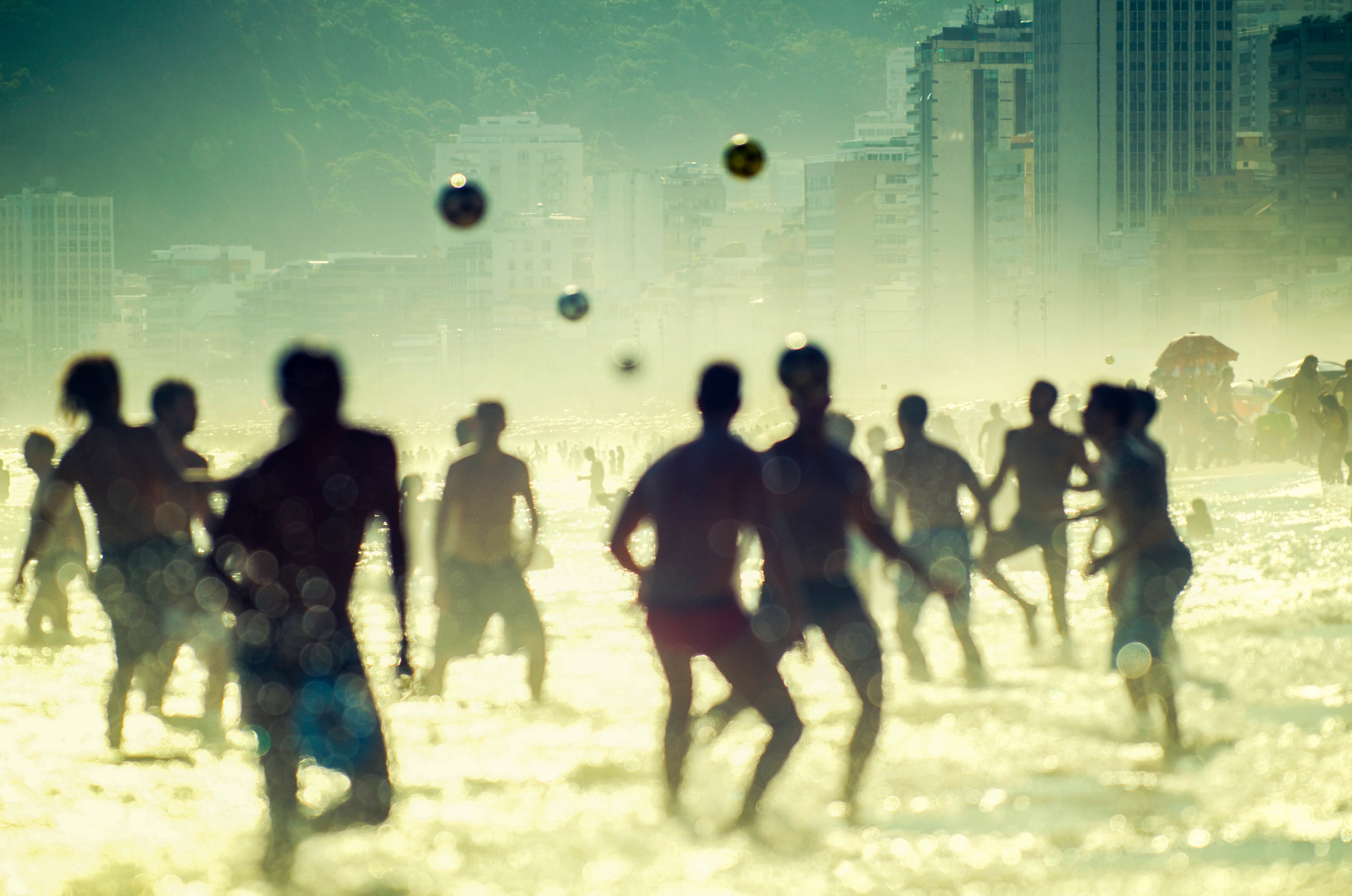 Brazilian people playing soccer football in a golden sunset afternoon at Posto Nove on Ipanema Beach Rio de Janeiro Brazil