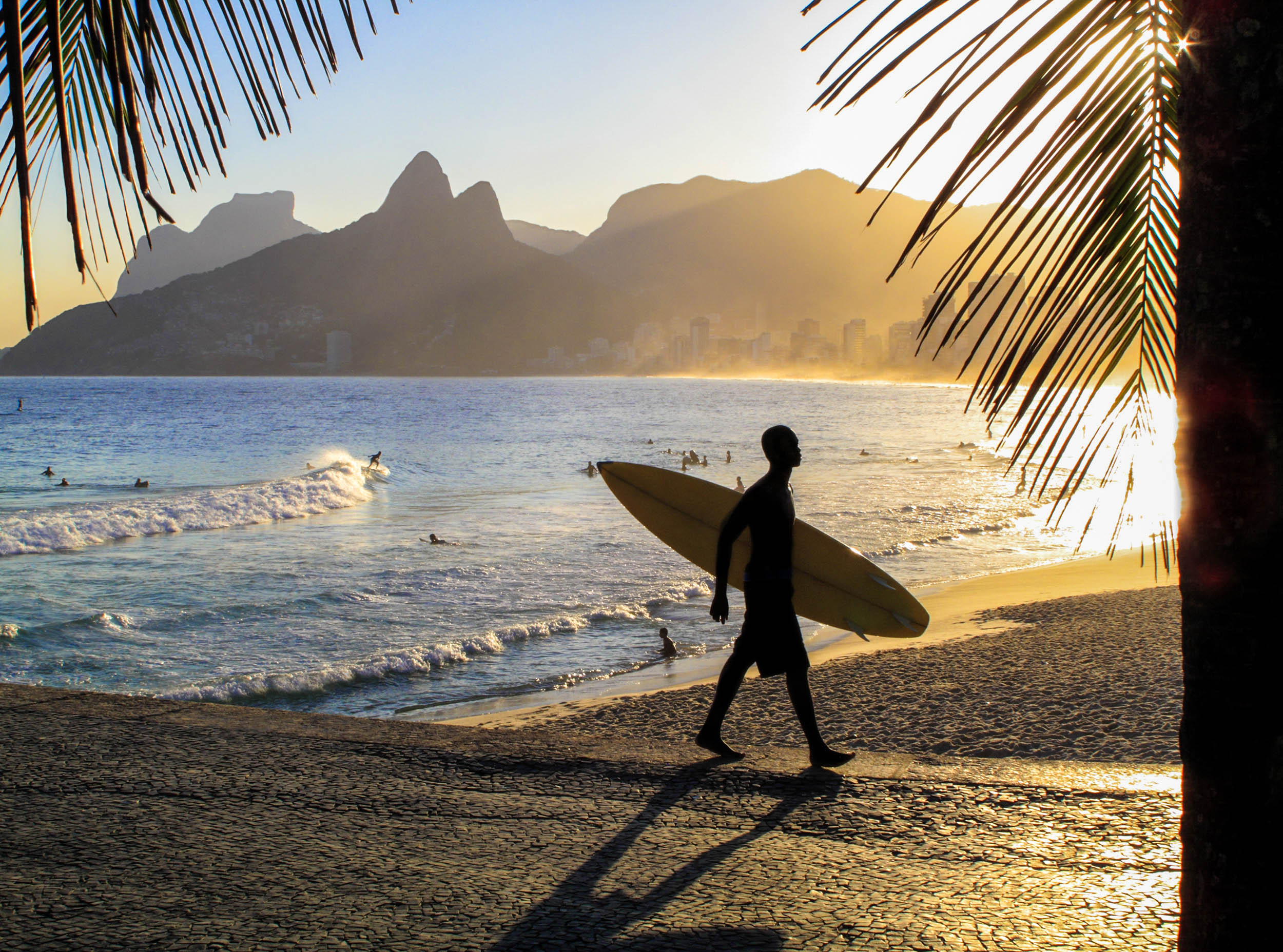 Surfer walking in Arpoador Beach. In the background, Pedra da Gavea and Two Brothers mountains.