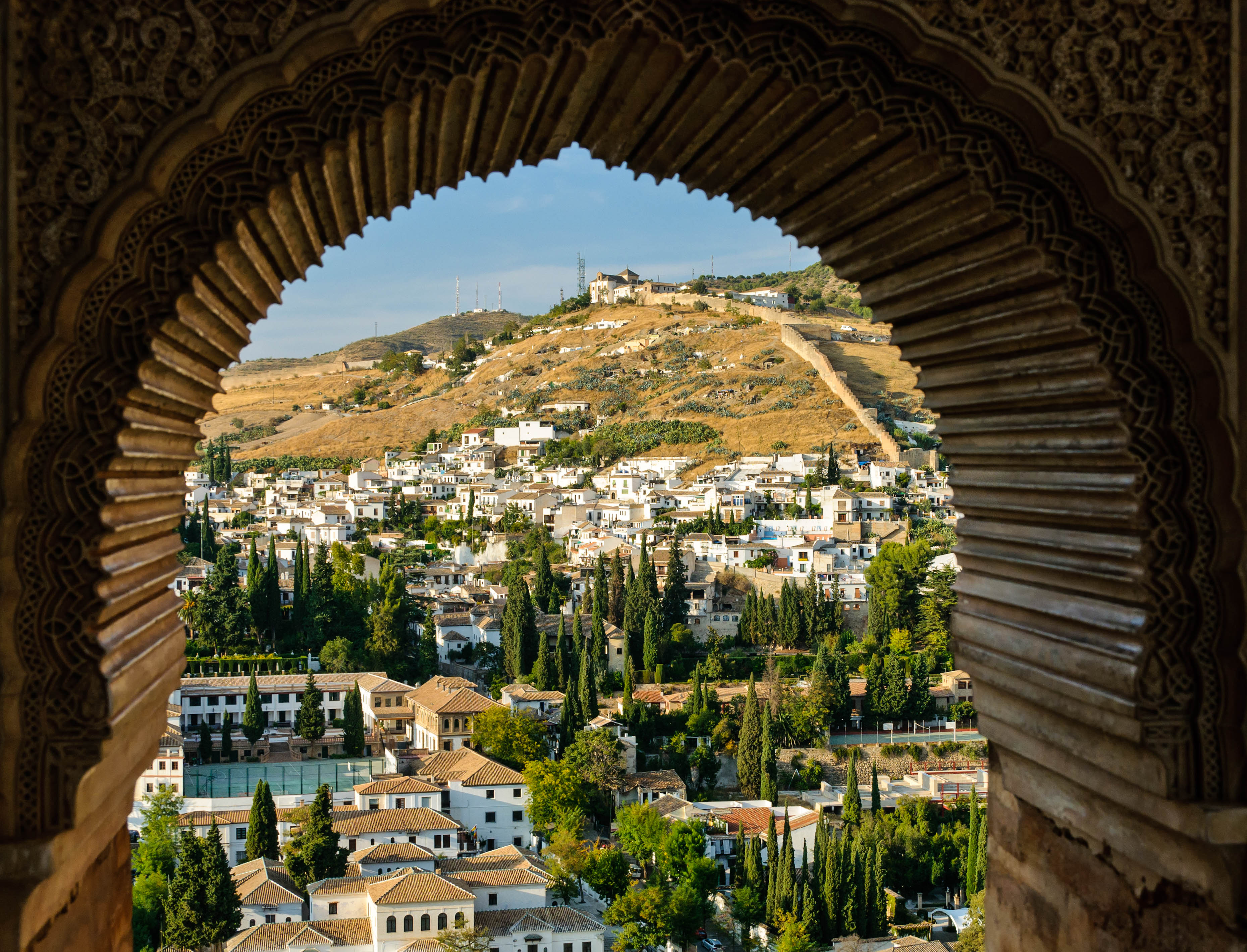 View of the typical white houses of the districts of Albaicin and Sacromonte from the Nasrid Palace (part of the Alhambra complex) in Granada, Spain