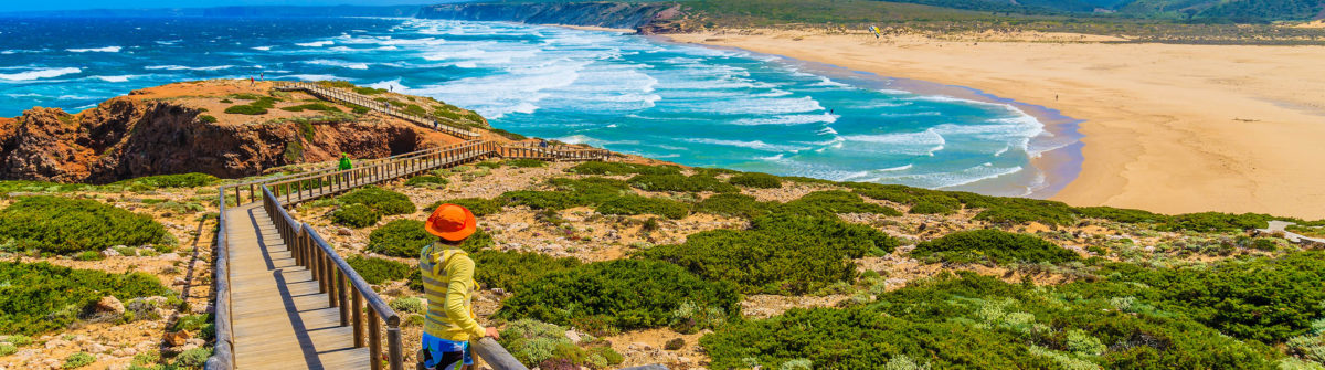 Young woman tourist on walkway to Praia do Bordeira beach shutterstock_280701572-2