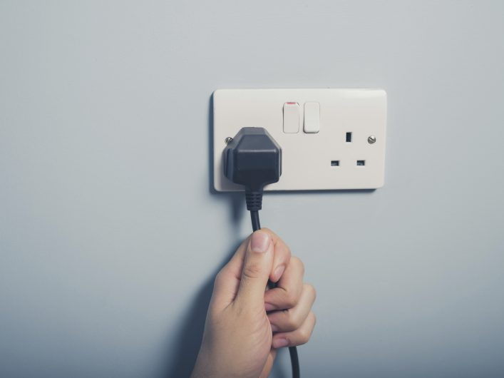 Male hand pulling a black cord from a white outlet