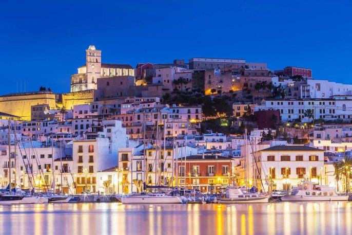 Ibiza-Dalt-Vila-downtown-at-night-with-light-reflections-in-the-water-Ibiza-Spain.-shutterstock_585352154