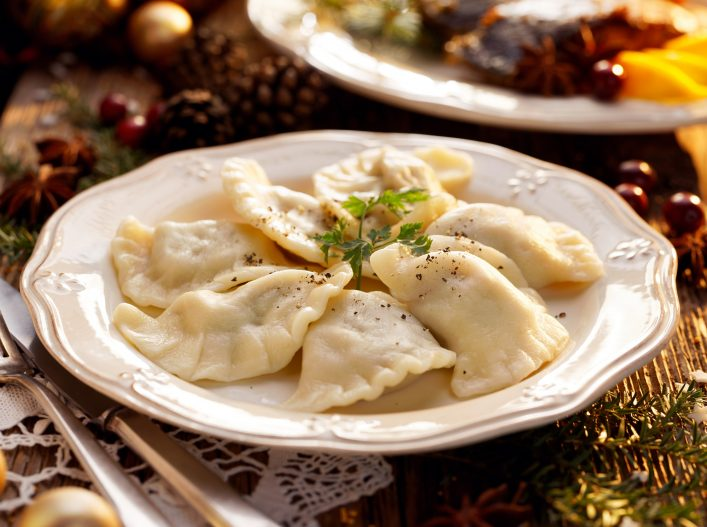 Dumplings stuffed with mushroom and cabbage on a white plate on wooden table.Traditional Christmas eve dish in Poland_shutterstock_749518531 klein