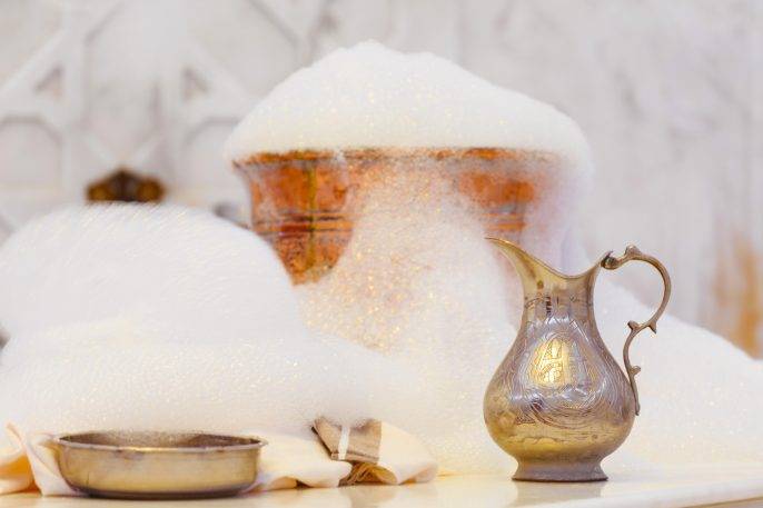 Water jar, towel and copper bowl with soap foam in turkish hamam. Traditional interior details