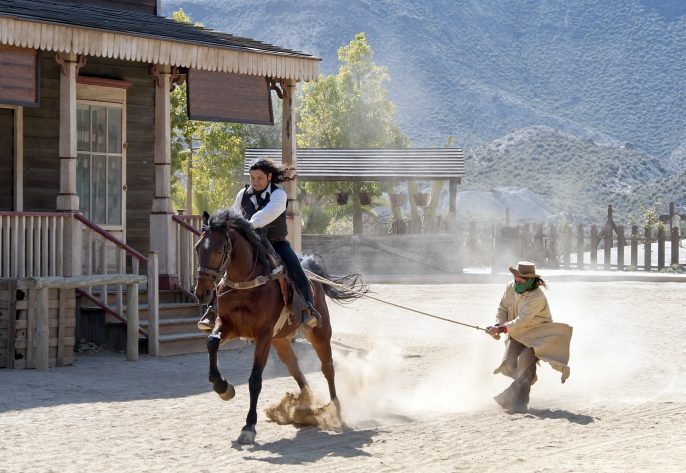 Cowboy-sheriff-dragging-a-Bandit-by-rope-at-Mini-Hollywood-Tabernas-Almeria-Province-Andalusia-Spain_97674353
