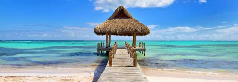 Tropical-white-sandy-beach.-Palm-leaf-roofed-wooden-pier-with-gazebo-on-the-beach.-Punta-Cana-Dominican-Republic-shutterstock_583369816