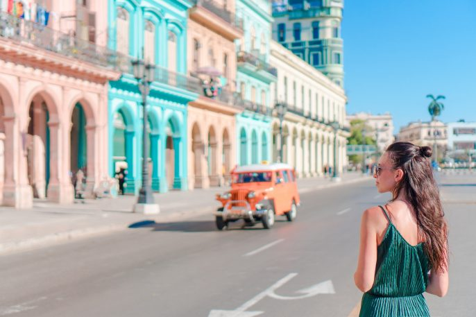 Happy woman in popular area in old Havana, Cuba. Young girl traveler background colorful houses shutterstock_642346180