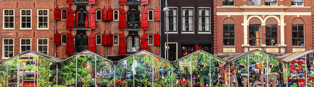 Amsterdam street traditional ancient dutch colorful buildings and flower market on Single canal shutterstock_237479155-2