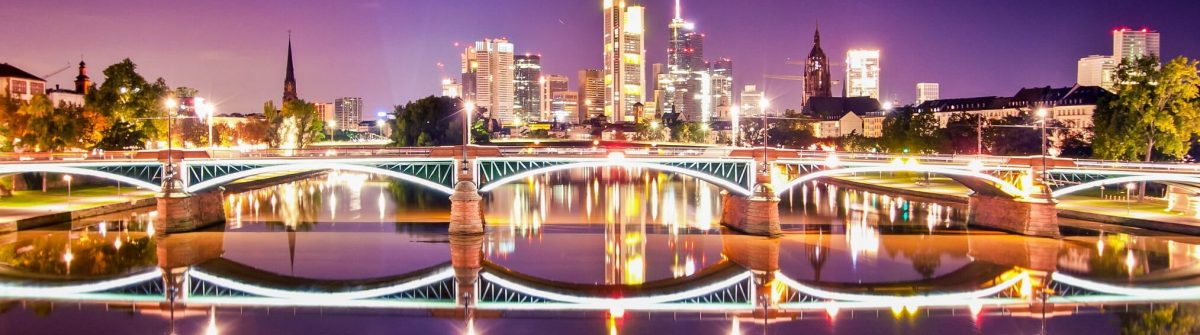 frankfurt-skyline-at-night-with-lighted-bridge-and-reflection-in-the-water-shutterstock_71730508-2