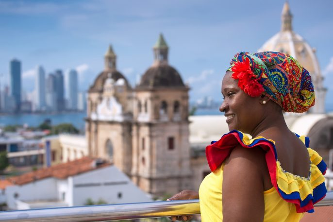 Woman-in-traditional-costume-against-the-backdrop-of-Cartagena-de-Indias-Colombia_514737343
