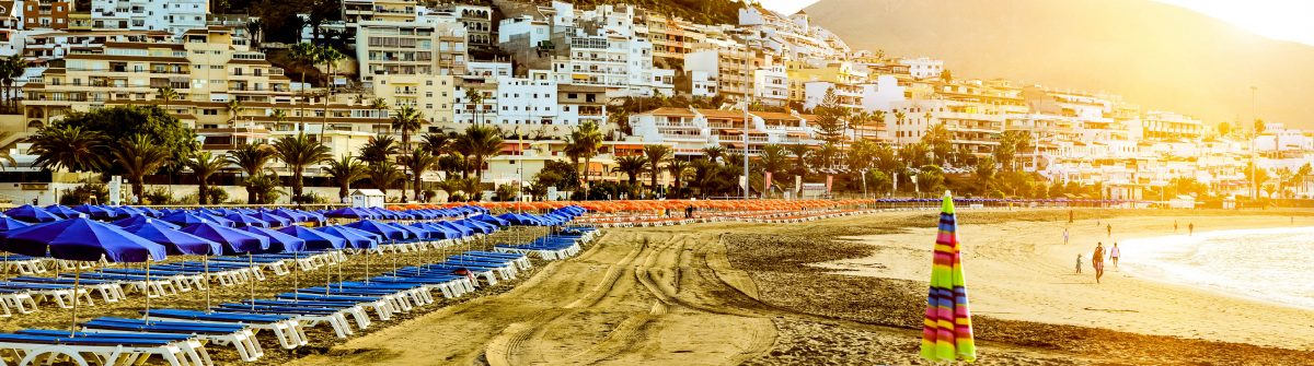 Sandy beach with blue parasols and sunbeds, Los Cristianos, Tene