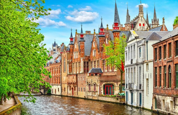 Medieval-town-Bruges-in-Belgium.-Panorama-and-landscape-vintage-channel-with-old-brick-house-broach-on-roof.-Spring-sunny-day-blue-sky-white-cloud-end-green-trees._650360299