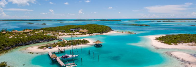 Aerial-view-of-exotic-island-with-authentic-buildings-and-pier-for-yachts._492232798