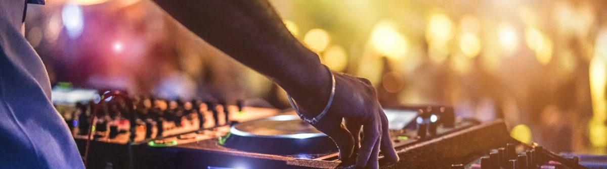 Dj-mixing-outdoor-at-beach-party-festival-with-crowd-of-people-in-background-shutterstock_670249444