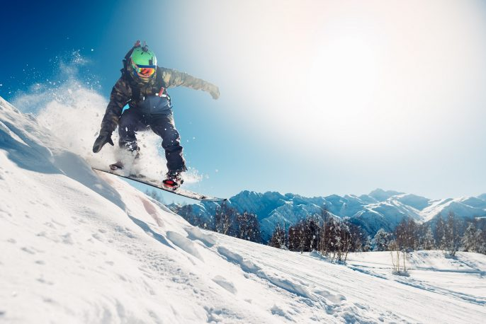snowboarder-is-jumping-with-snowboard-from-snowhill-shutterstock_598921001