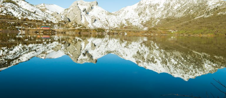 The-hills-covered-with-snow-are-reflected-in-a-lake-of-Barrios-De-Luna-Leon-Spain-on-a-beautiful-winter-evening-shutterstock_1297669267