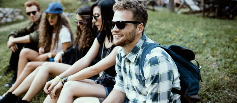 Festival_close-up-of-hipster-sitting-on-the-grass-with-his-friends_shutterstock_511609855