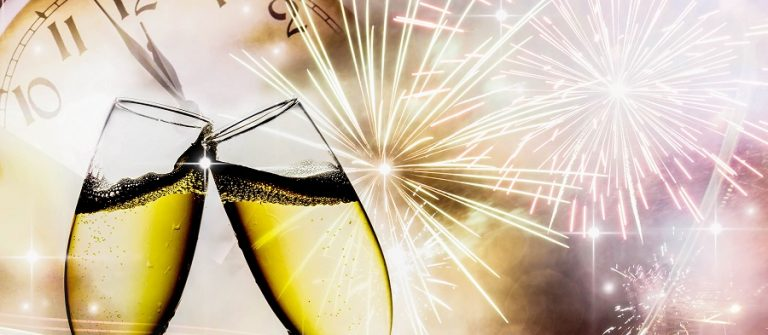 Glasses-with-champagne-against-fireworks-and-clock-close-to-midnight-shutterstock_122288275_900x600