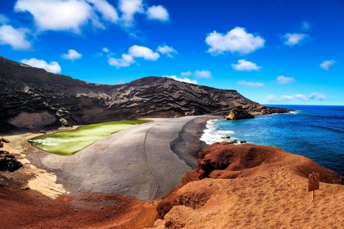 View-into-a-volcanic-crater-with-its-green-lake-near-El-Golfo-Lanzarote-island_shutterstock_579556312-1920×1280-1