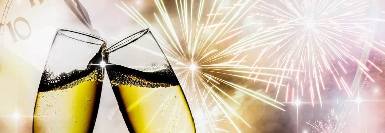 Glasses-with-champagne-against-fireworks-and-clock-close-to-midnight-shutterstock_122288275-2_1920x1280