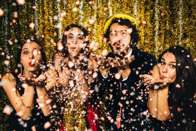 Friends blowing confetti on New Year's Eve – 2016.