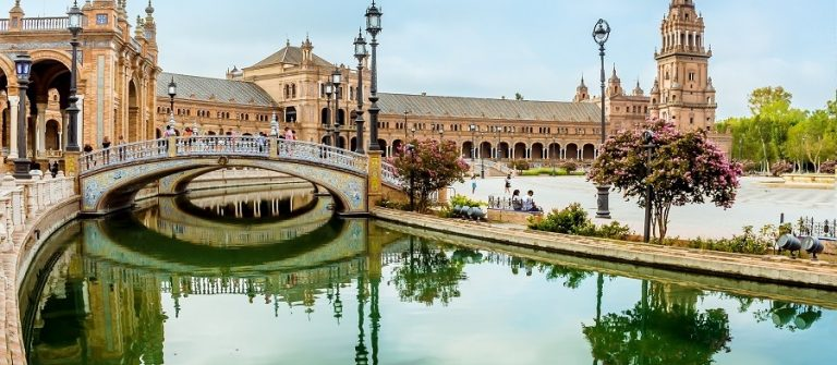 A-view-along-a-canal-towards-the-southern-side-of-the-Plaza-de-Espana-in-Seville-Spain-in-the-stillness-of-the-early-morning-in-summertime-shutterstock_1190502871