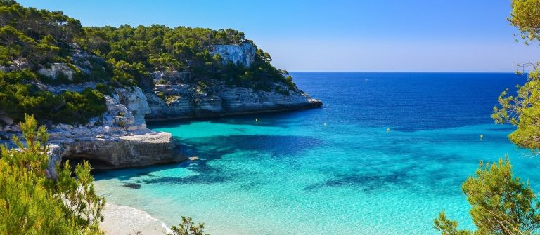 Secluded-beach-with-turquoise-sea-water-Cala-Mitjaneta-Menorca-island-Spain-shutterstock_189270002-min-1
